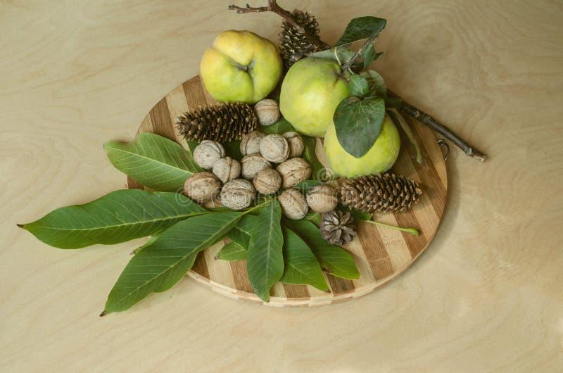 Tablero de la cocina con las frutas del otoño, el membrillo con las hojas marchitadas, un puñado en de nueces de la cáscara y los imagen de archivo