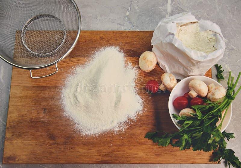 Tablero de la cocina con los ingredientes para cocinar la pizza fotografía de archivo libre de regalías