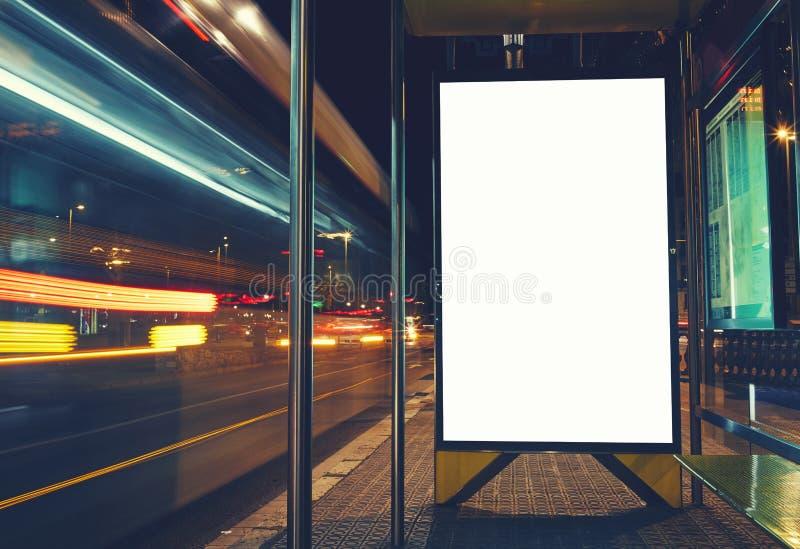 Tablero de la información pública con los vehículos borrosos en velocidad en ciudad de la noche imagen de archivo libre de regalías