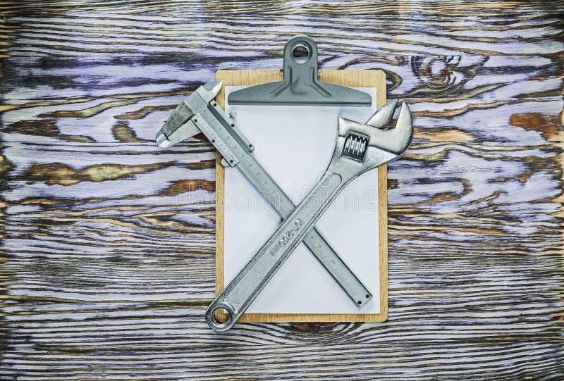 Tablero de la llave ajustable del calibrador a vernier en el tablero de madera foto de archivo
