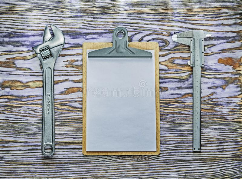 Tablero de la llave inglesa ajustable del calibrador a vernier en el tablero de madera fotos de archivo libres de regalías