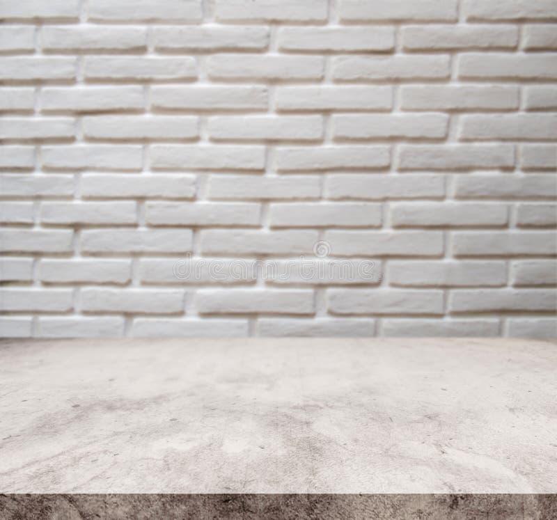 Tablero de la mesa de piedra de mármol blanco, con el fondo blanco de la textura de la pared del ladrillo del defocus foto de archivo