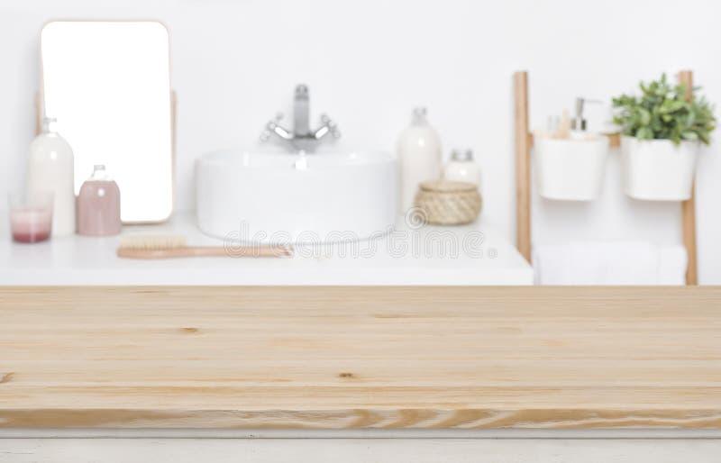 Tablero de la mesa de madera para la exhibición del producto sobre fondo interior del cuarto de baño defocused foto de archivo libre de regalías