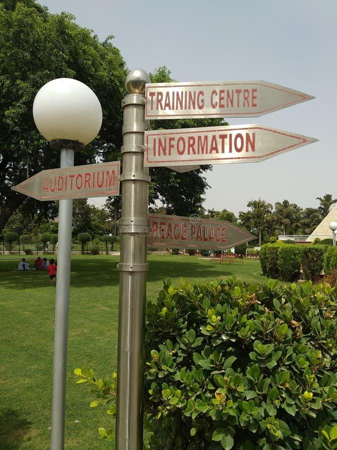 Tablero de la muestra en un parque para las direcciones imagenes de archivo