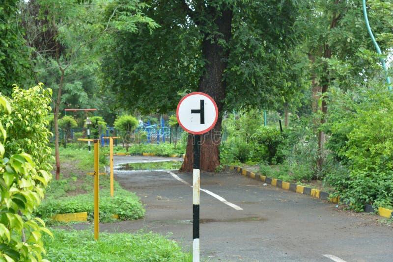 Tablero de la señal de tráfico en jardín imágenes de archivo libres de regalías