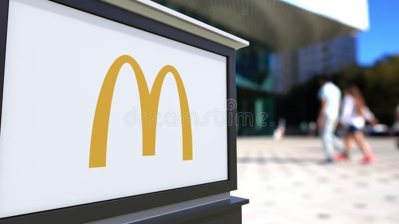 Tablero de la señalización de la calle con el logotipo del ` s de McDonald Centro borroso de la oficina y fondo de la gente que c stock de ilustración