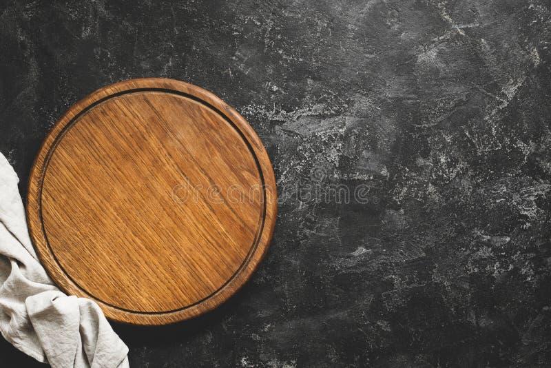 Tablero de la tabla de cortar de madera o de la pizza en fondo concreto negro imagen de archivo