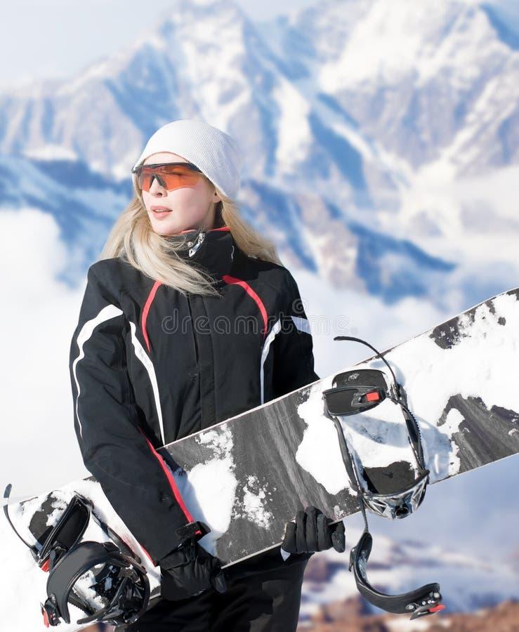 Tablero de la tenencia del snowboarder de la mujer a disposición en invierno de la nieve en la ladera en sonrisas negras de la ro imagen de archivo libre de regalías