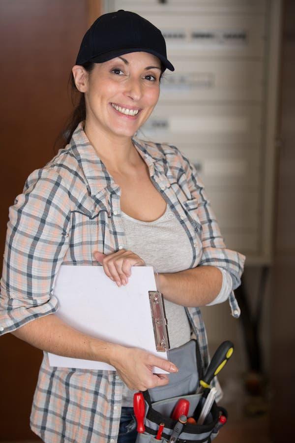 Tablero de la tenencia del trabajador de sexo femenino y toolbelt que lleva foto de archivo