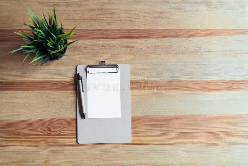 Tablero de la visión superior con la pluma y Libro Blanco en el fondo de la tabla imagenes de archivo