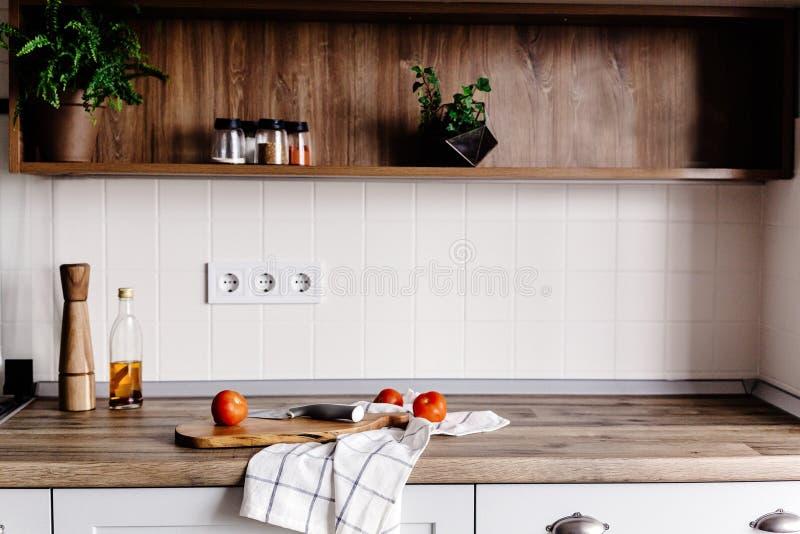 Tablero de madera con el cuchillo, aceite de oliva, tomates, toalla en ki moderno imagen de archivo libre de regalías
