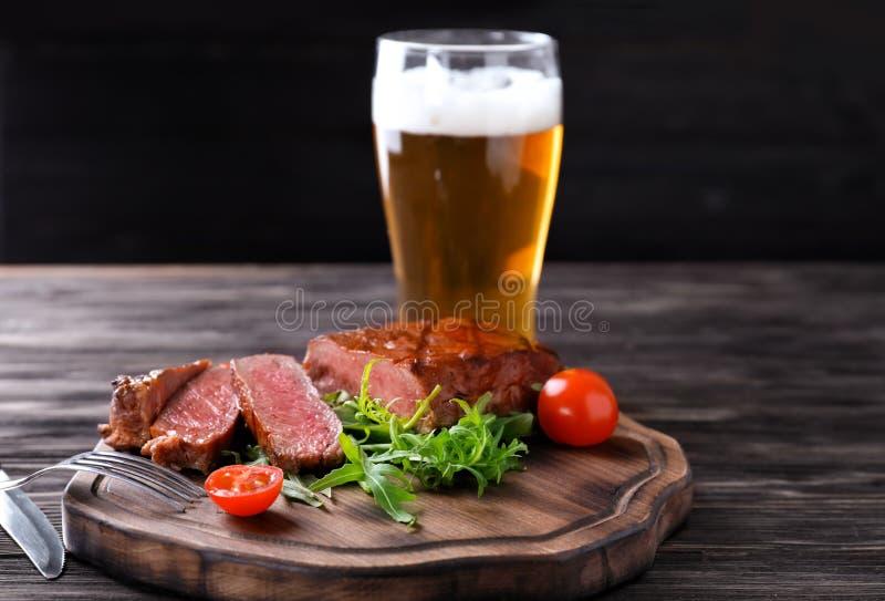 Tablero de madera con el filete y el vaso de cerveza asados a la parrilla sabrosos en la tabla fotos de archivo