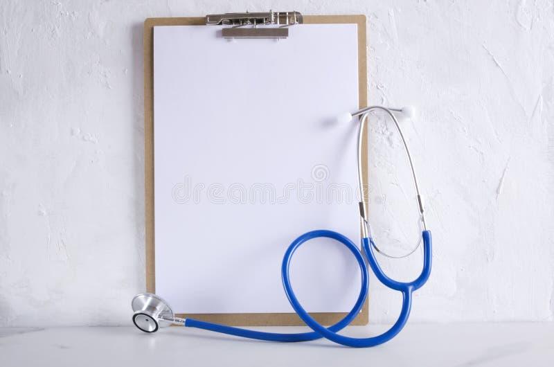 Tablero de madera con el papel en blanco para el texto y el estetoscopio en el escritorio blanco en el hospital fotos de archivo libres de regalías