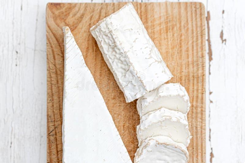 Tablero de madera con el queso de cabra blanco en fondo brillante Disco del queso imagen de archivo