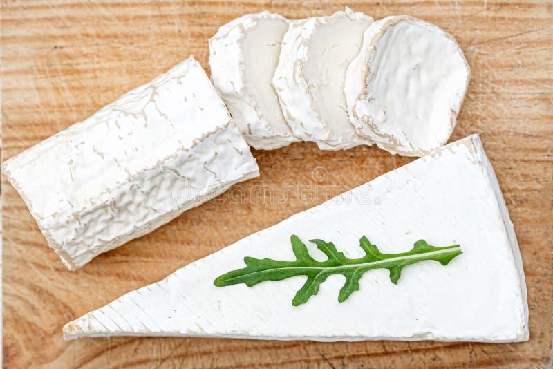 Tablero de madera con el queso de cabra blanco en fondo brillante Disco del queso imagen de archivo libre de regalías