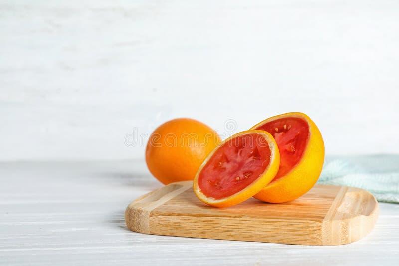 Tablero de madera con el tomate que revela anaranjado cortado dentro en la tabla foto de archivo