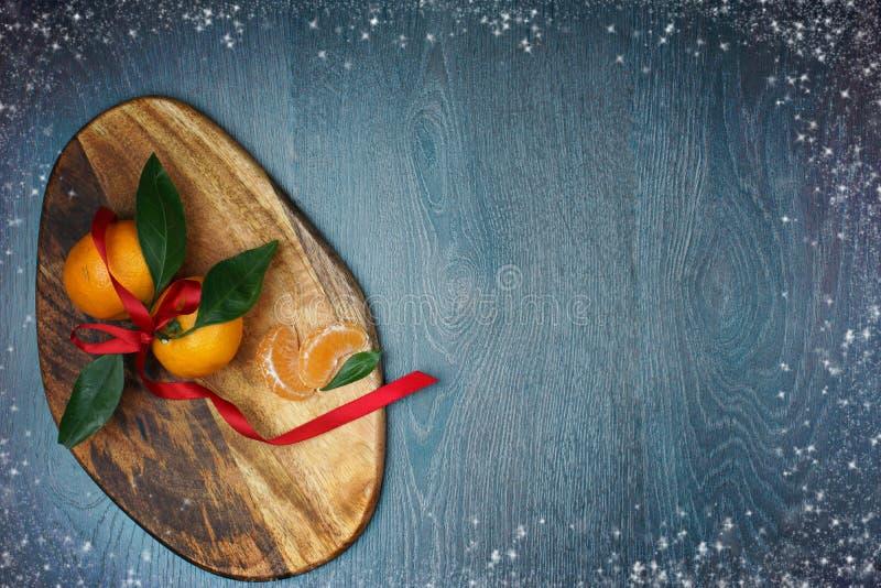 Tablero de madera con las mandarinas con las hojas verdes y con una cinta roja, un marco del brillo y nieve a lo largo del borde fotografía de archivo