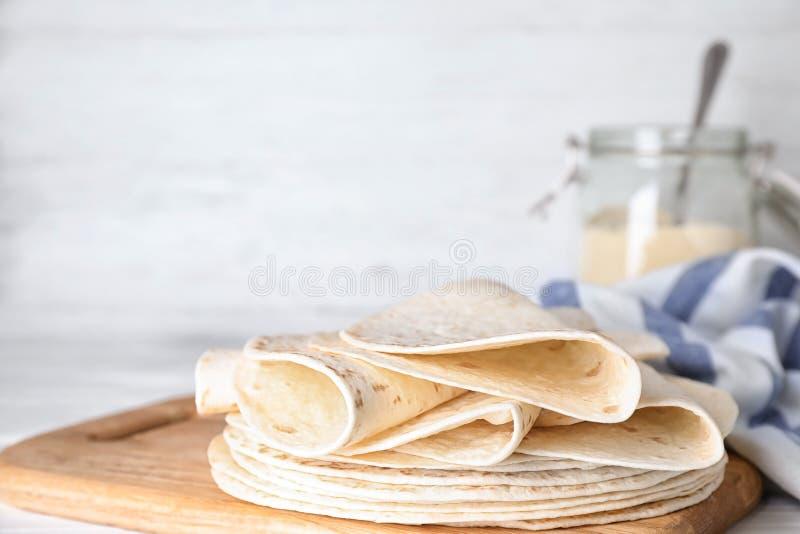 Tablero de madera con las tortillas de maíz en la tabla Pan ?cimo foto de archivo