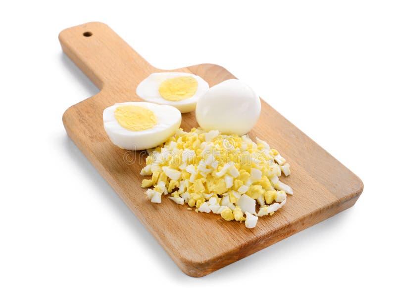 Tablero de madera con los huevos hervidos enteros y del corte en el fondo blanco imagen de archivo