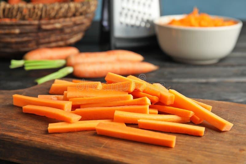 Tablero de madera con los palillos de zanahoria imágenes de archivo libres de regalías