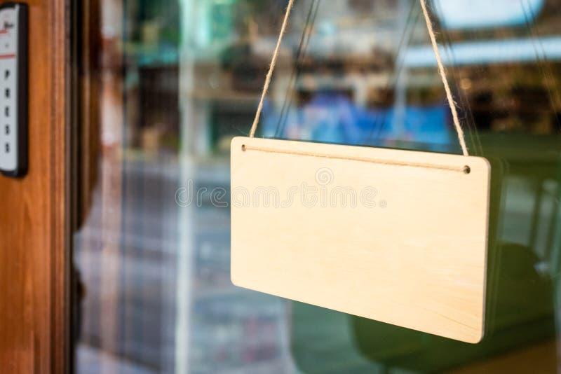 Tablero de madera en blanco de la muestra con la cuerda que cuelga en puerta fotografía de archivo libre de regalías