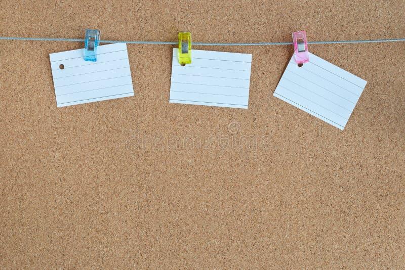 Tablero de memoria del corcho con las paces en blanco del papel que cuelgan en cuerda con el perno de ropa, horizontales foto de archivo