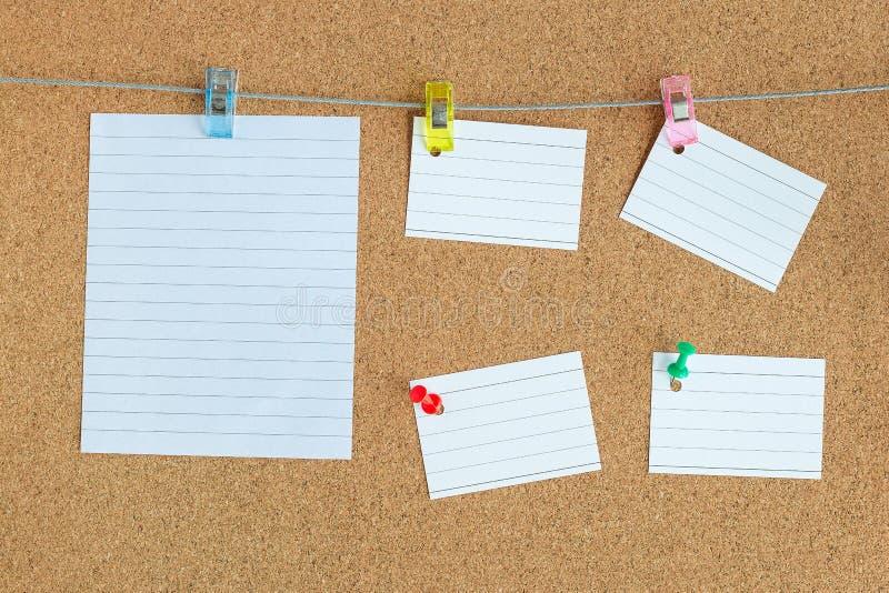 Tablero de memoria del corcho con las paces en blanco del papel que cuelgan en la cuerda con el perno de ropa y fijada en el tabl fotografía de archivo