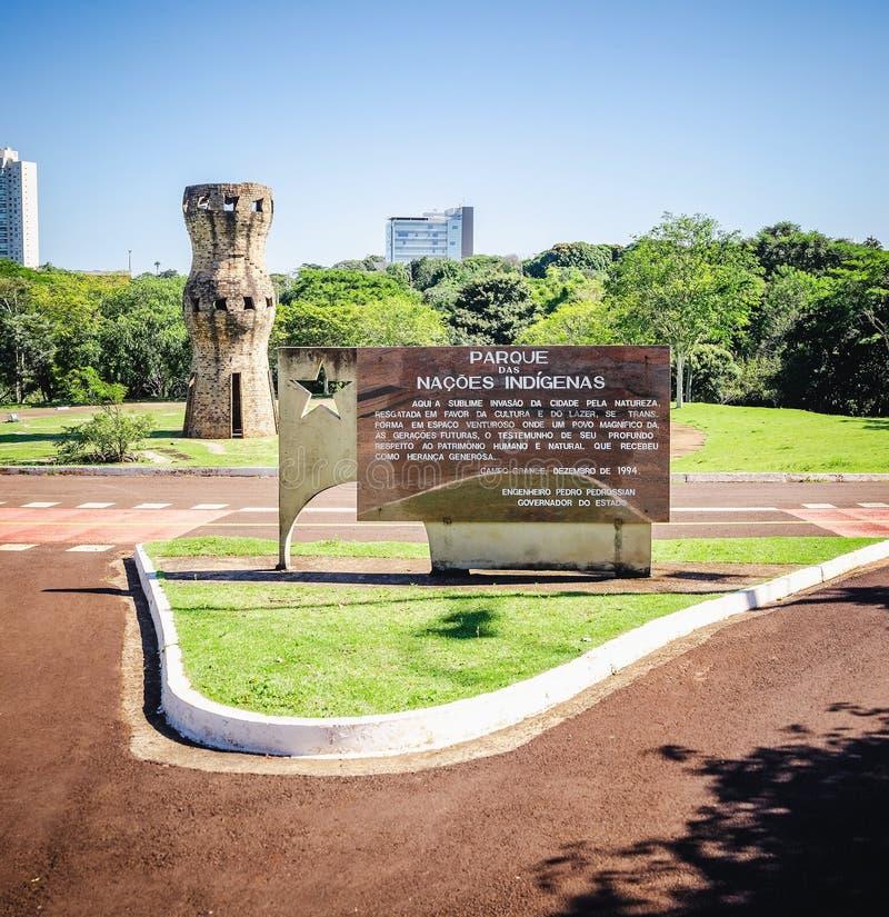 Tablero de mensajes en la entrada y el monumento del Peo indígena foto de archivo