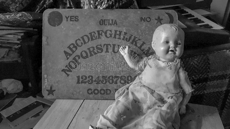 Tablero de Ouija y muñeca espeluznante fotografía de archivo
