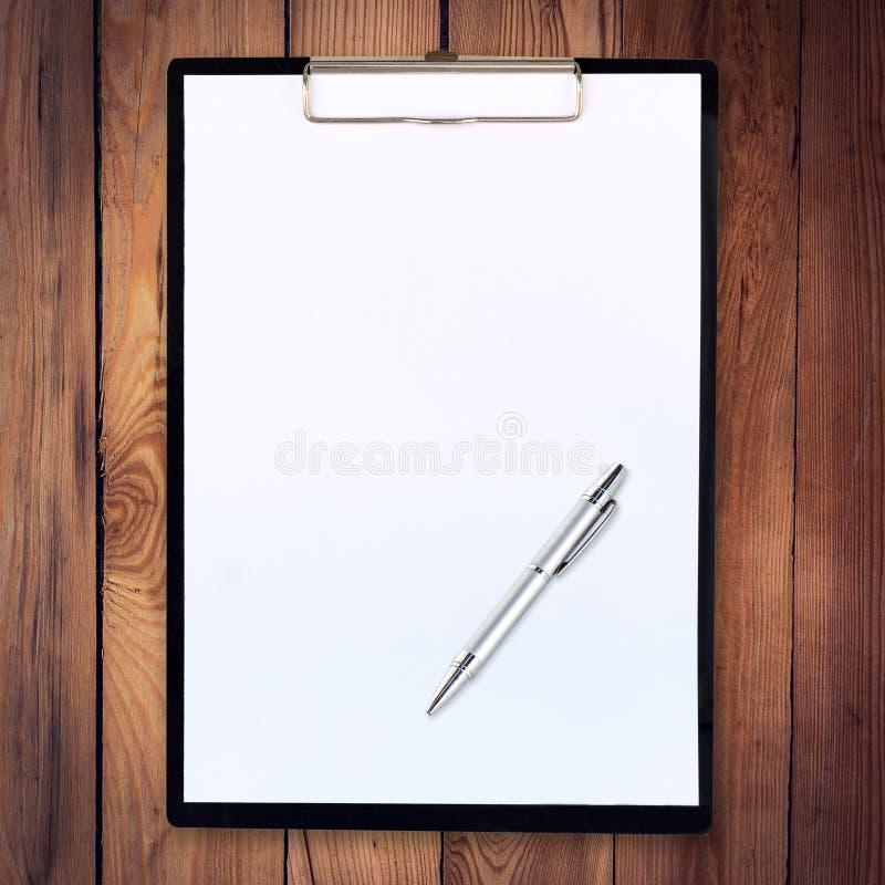 Tablero de papel en el fondo de madera con la pluma foto de archivo libre de regalías