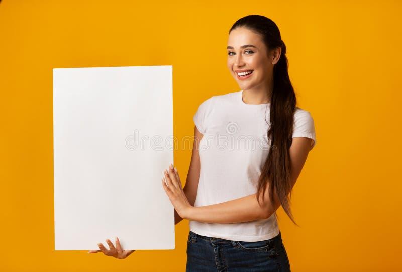 Tablero de señora joven Holding Blank White en fondo amarillo imagen de archivo libre de regalías