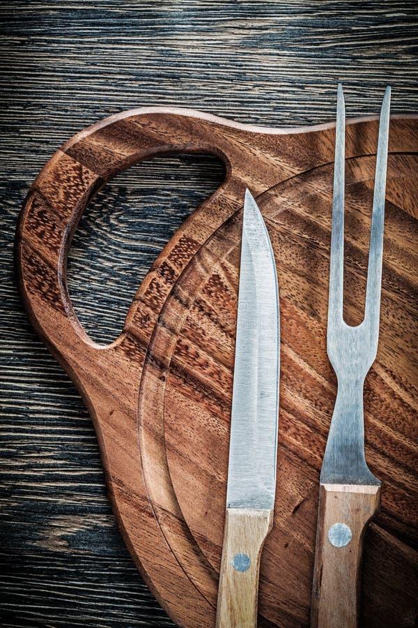 Tablero de talla de madera del cuchillo de la bifurcación de la carne en el fondo de madera imagen de archivo