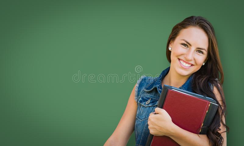Tablero de tiza en blanco detrás del estudiante Holding Books de la chica joven de la raza mixta fotografía de archivo libre de regalías