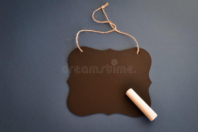 Tablero de tiza de madera negro modelado con un pedazo de tiza en un fondo azul marino conveniente para saludar, el mensaje, menú fotografía de archivo libre de regalías