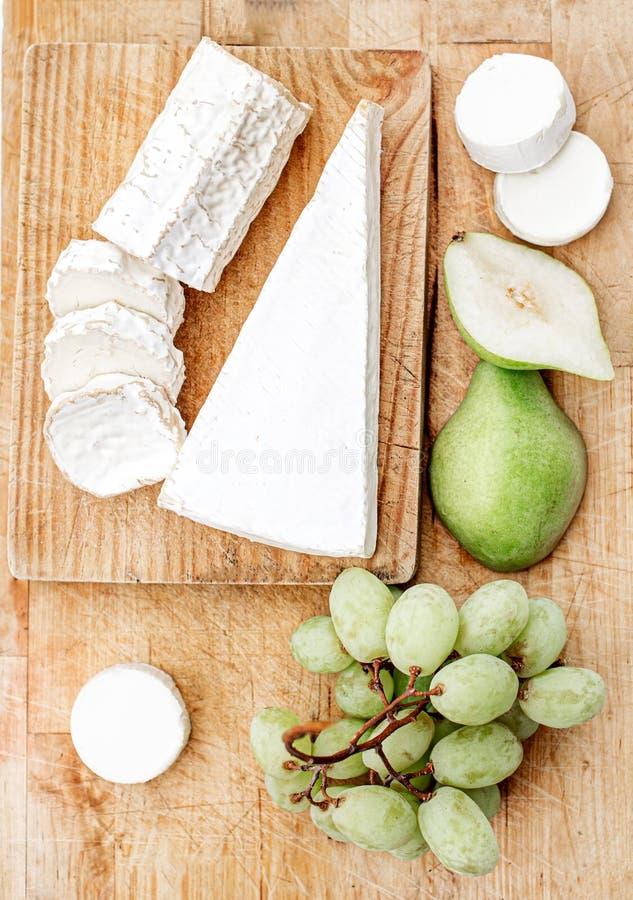 Tablero del queso con diversos queso, pera y uvas en el fondo de madera blanco Opini?n superior del disco del queso Copie el espa fotos de archivo
