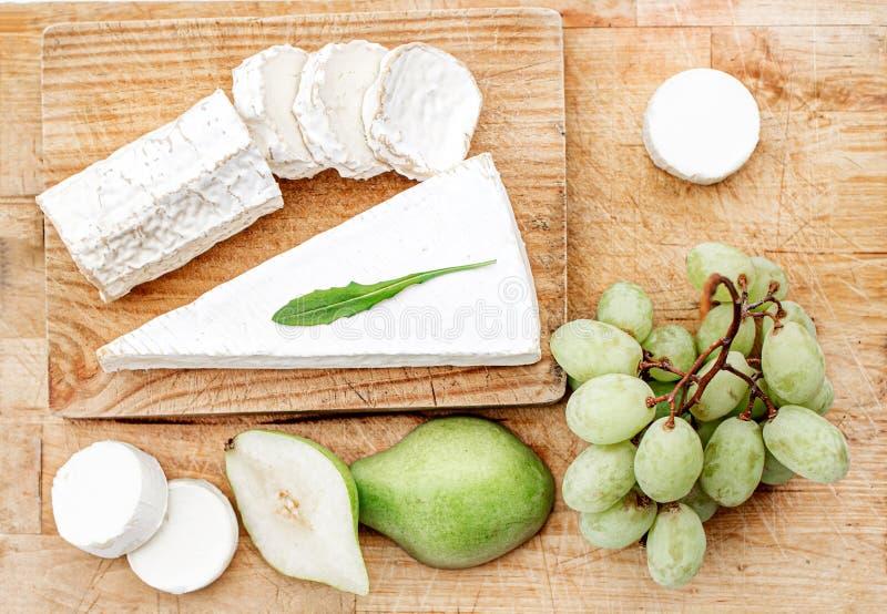 Tablero del queso con diversos queso, pera y uvas en el fondo de madera blanco Opini?n superior del disco del queso Copie el espa imagenes de archivo