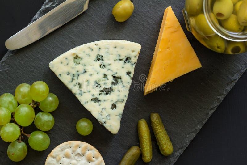 Tablero del queso con el queso de molde azul, Cheddar amarillo, aceitunas, grap imagen de archivo libre de regalías
