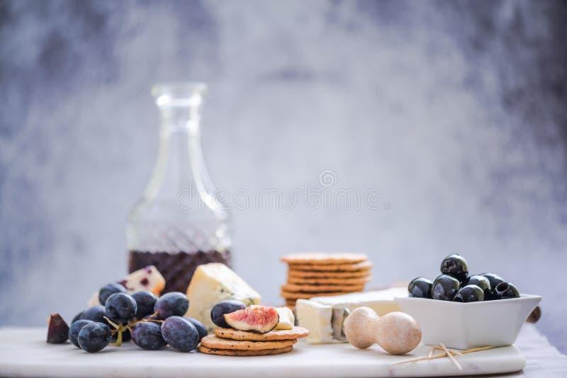 Tablero del queso con las uvas, el vino, el higo y las aceitunas foto de archivo