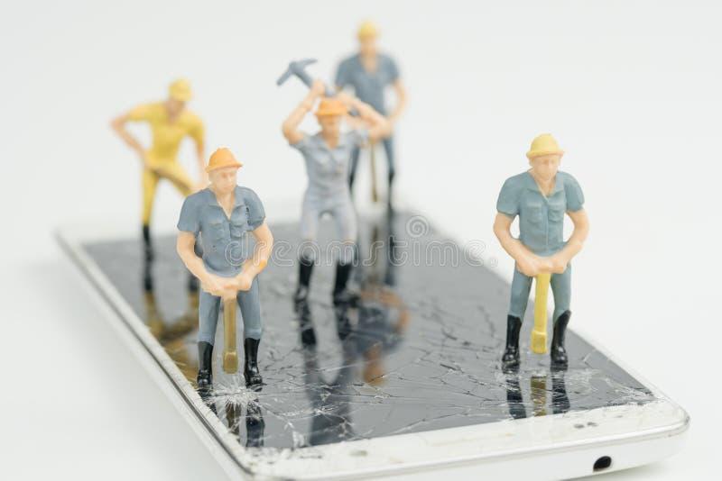 Tablero electrónico con la figura miniatura trabajador fotos de archivo