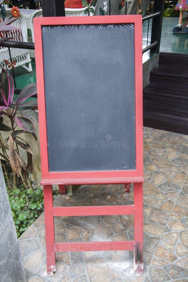 Tablero en blanco del menú de la muestra de la pizarra con el marco rojo y soporte rojo delante del restaurante fotografía de archivo libre de regalías