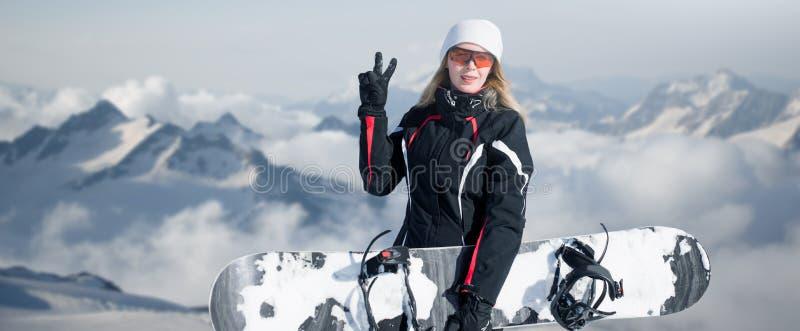 Tablero joven de la tenencia del snowboarder de la mujer adulta a disposición en invierno de la nieve en la ladera en sonrisas ne fotos de archivo libres de regalías