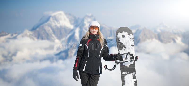 Tablero joven de la tenencia del snowboarder de la mujer adulta a disposición en invierno de la nieve en la ladera en sonrisas ne fotografía de archivo libre de regalías