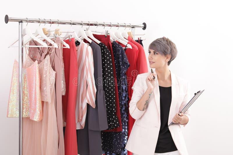 Tablero joven hermoso de la tenencia del estilista cerca del estante con ropa de diseñador imagen de archivo libre de regalías