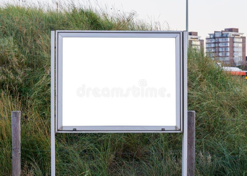 Tablero metálico vacío y en blanco de la información para poner lo que usted quiere nunca con una colina de la hierba verde en el fotos de archivo