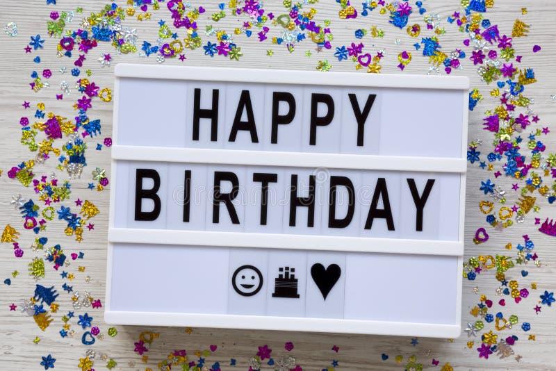 Tablero moderno con el texto 'feliz cumpleaños ', partido en un fondo de madera blanco, visión de arriba de la decoración Endecha imágenes de archivo libres de regalías