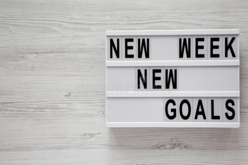 Tablero moderno con la superficie de madera blanca de las nuevas metas nueva semana del texto de la 'encima, visión de arriba Des fotos de archivo libres de regalías