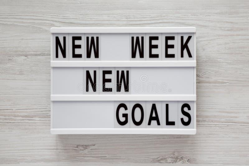 Tablero moderno con la superficie de madera blanca de las nuevas metas nueva semana del texto de la 'encima, visión superior Desd foto de archivo
