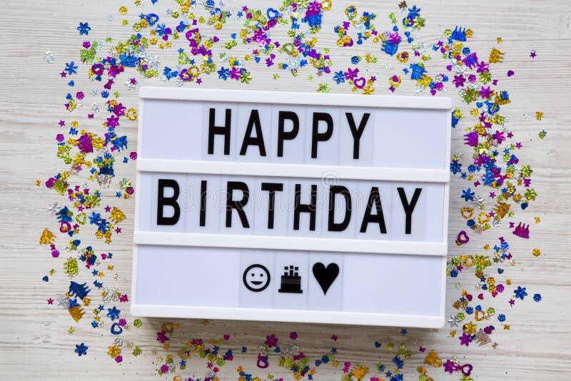 Tablero moderno con palabras del 'feliz cumpleaños ', partido de la decoración en el fondo de madera blanco, visión superior Ende imagen de archivo libre de regalías