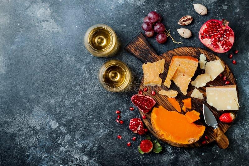 Tablero o disco de la variedad del queso con el surtido del queso, las uvas, la miel, las nueces y el vino en vidrios Ennegrezca  imagenes de archivo