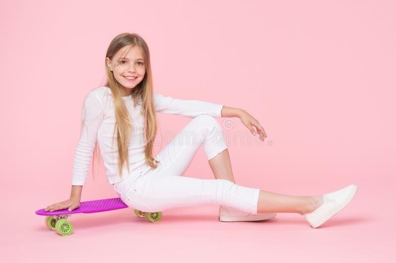 Tablero que monta en estilo para los años venideros Pequeño niño feliz que se sienta a bordo cubierta en fondo rosado Pequeño pat foto de archivo